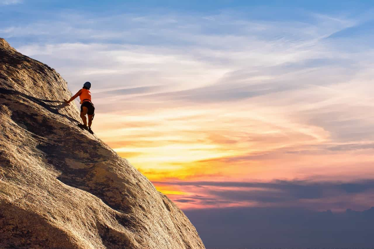 崖を登っている人と夕日の画像