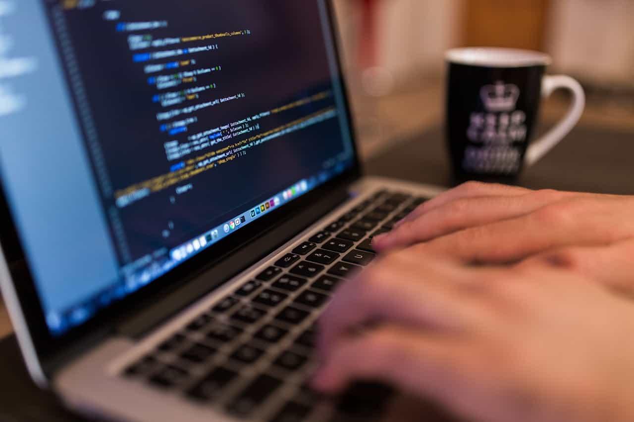 ラップトップとそのディスプレーに映るデジタルコード文字の画像