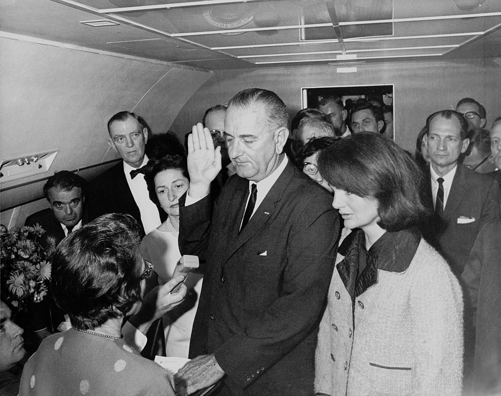 機内で大統領宣誓するジョンソン。隣はジャクリーン・ケネディ(1963年)